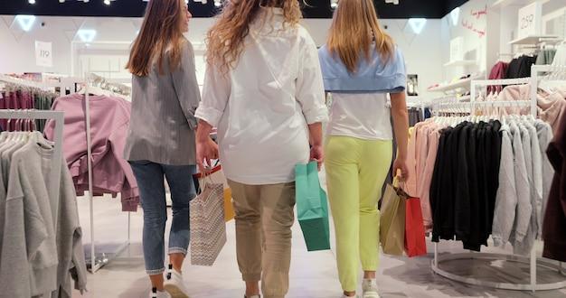 Niskie ujęcie trzech dziewczyn, które przechadzają się po sklepie odzieżowym w kolorowych ubraniach. koncepcja życia młodzieży, przyjaźni i konsumpcjonizmu.