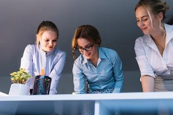 Niskiego kąta widok pracuje na biurku w biurze uśmiechnięty bizneswoman