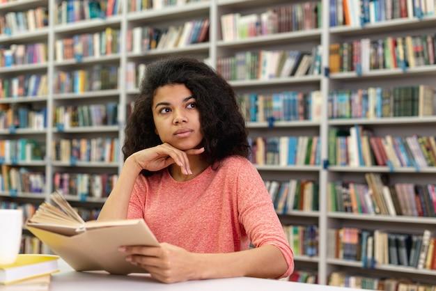 Niskiego kąta dziewczyna przy bibliotecznym czytaniem