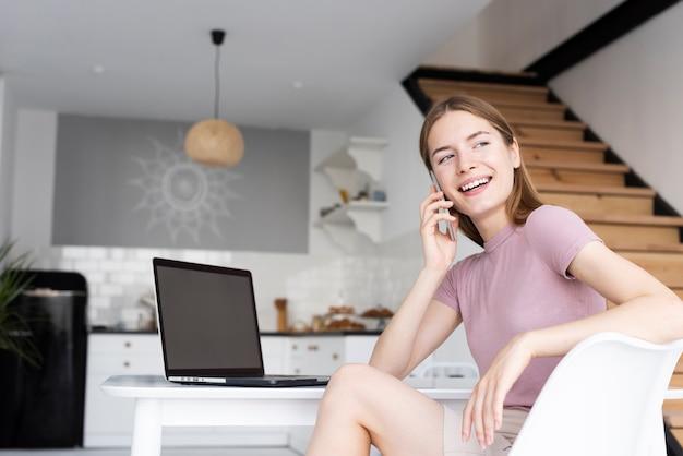 Niskiego kąta kobiety obsiadanie przy jej biurkiem