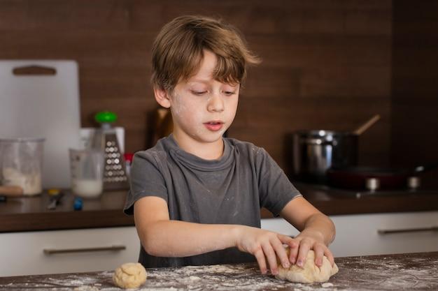 Niskiego kąta mały chłopiec robi ciastu