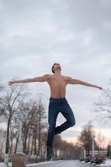 Niskiego kąta młody człowiek wykonuje baletniczy plenerowego