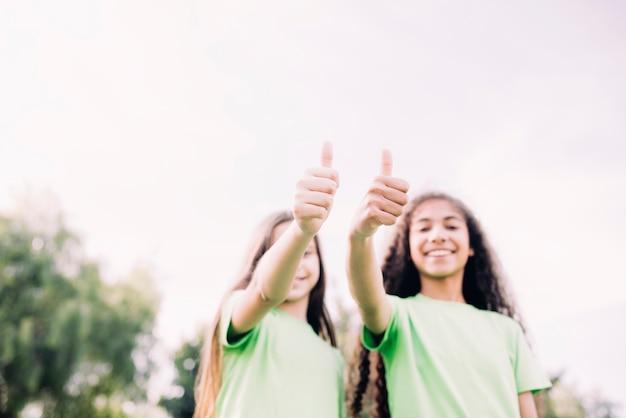 Niskiego kąta widok śliczne dziewczyny pokazuje kciuka up gest przeciw niebu