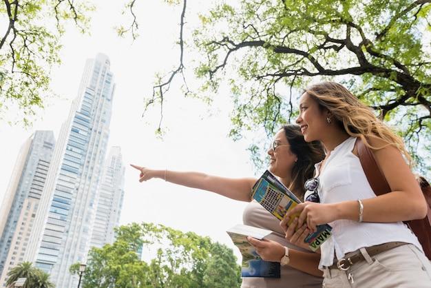 Niskiego kąta widok żeńska mienie mapa w rękach patrzeje jej kobiety wskazuje przy coś