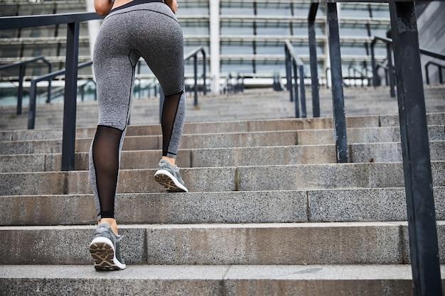 Nisko przycięta głowa kobiety w sportowych legginsach pędzi na górę do uprawiania sportu w centrum miasta