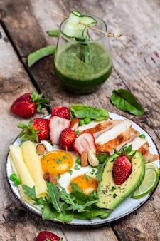 Niskowęglowodanowe śniadanie o wysokiej zawartości tłuszczu, grillowany filet z kurczaka i awokado, jajka sadzone z truskawkami, serem i orzechami. smoothie detox, świeża zieleń, dieta ketogeniczna. koncepcja zdrowej żywności, widok z góry