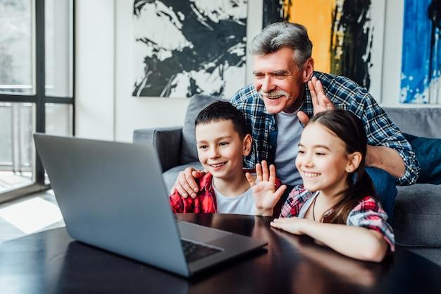 No hej. pozytywnie nastawiony emerytowany mężczyzna i jego małe wnuki uśmiechają się i machają rękami podczas rozmowy wideo w domu.