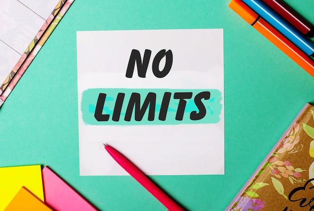 No limits napisane na turkusowej powierzchni w pobliżu jasnych naklejek, notatników i markerów