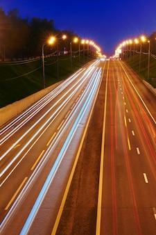 Noc autostrada droga ze światłami samochodów. żółto-czerwony szlak świetlny na jezdni o dużej prędkości ruchu. . długa ekspozycja abstrakcyjne tło miejskie