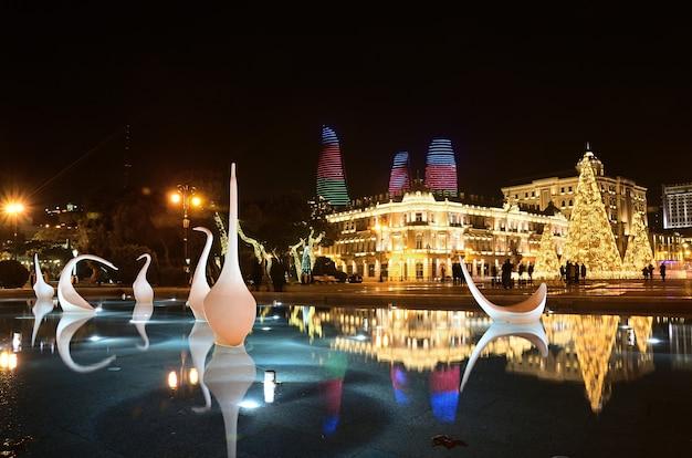 Noc baku w nowym roku ze świecącą choinką ozdobioną wzorami i fontanną łabędzi na pierwszym planie.
