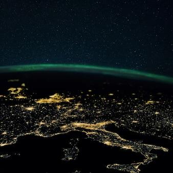 Noc planeta ziemia ze światłami miast megalopolis w nocy i zorzę polarną. europa i miasta włoch, francji, hiszpanii i niemiec, widok z kosmosu.