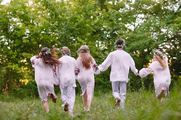 Noc przesilona, ludzie biegający w naturze w słowiańskich ubraniach.