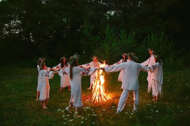 Noc świętojańska, młodzi ludzie w słowiańskich kręgach odzieżowych tańczą wokół ogniska w lesie.