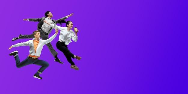 Noc. szczęśliwi pracownicy biurowi skaczą i tańczą w zwykłych ubraniach lub garniturze na tle gradientowego płynu neonowego. biznes, start-up, praca w otwartej przestrzeni, ruch, koncepcja działania. kreatywny kolaż.