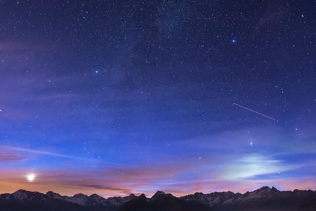 Noc w alpach pod gwiaździstym niebem i światłem księżyca