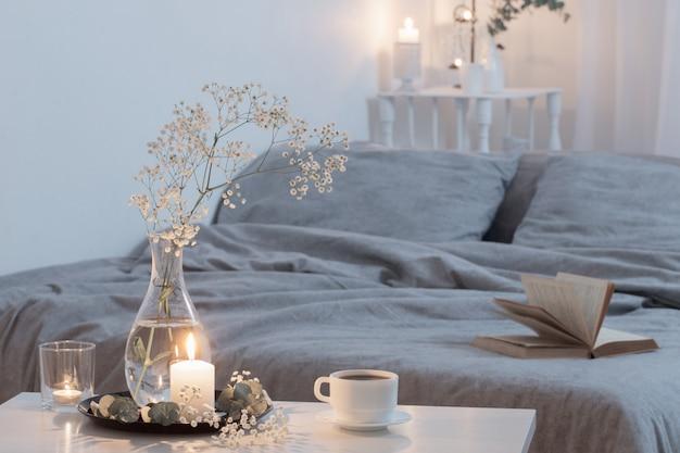 Noc wnętrze sypialni z kwiatami i płonącymi świecami