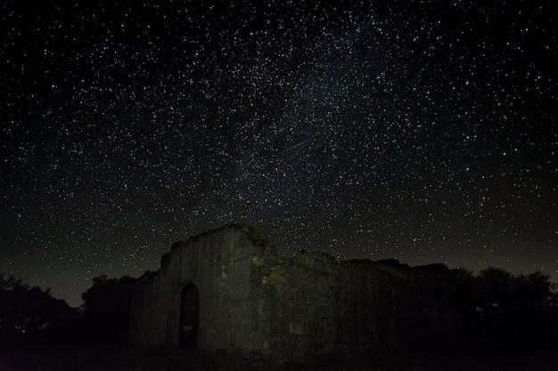 Nocna fotografia z ruinami starożytnej pustelni położonej w pobliżu guijo de granadilla. ermita de hojaranzo. estremadura, hiszpania.