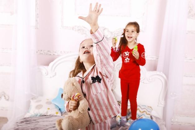 Nocna impreza dla dzieci, śmieszne szczęśliwe siostry ubrane w jasną piżamę, gra w bąbelki