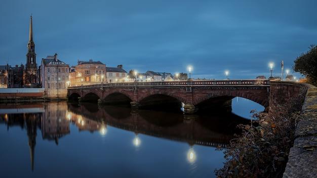 Nocna panorama mostu nad rzeką ayr i nabrzeża przy ayr latarnie miejskie światło ayr sc...