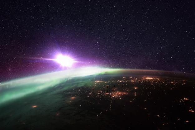 Nocna planeta ziemia z niesamowitymi zielonymi światłami polarnymi i fioletową gwiaździstą przestrzenią z jasną gwiazdą. jasne światła miejskie megamiast, widok z kosmosu