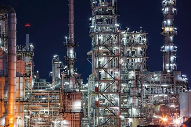 Nocna scena rafinerii ropy naftowej i kolumny wieży przemysłu petrochemicznego w budowie terenu