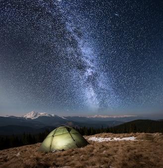 Nocne biwakowanie. podświetlany namiot turystyczny pod pięknym nocnym niebem pełnym gwiazd i mlecznej drogi. na tle zaśnieżone góry i lasy