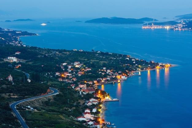 Nocne lato na wybrzeżu chorwackiego półwyspu peljeåac (viganj, chorwacja), a w oddali wioska i wyspa korcula.