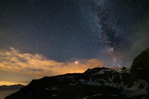 Nocne niebo astro, gwiazdy drogi mlecznej nad alpami, burzliwe niebo, planeta mars poza chmurami, ośnieżone pasmo górskie