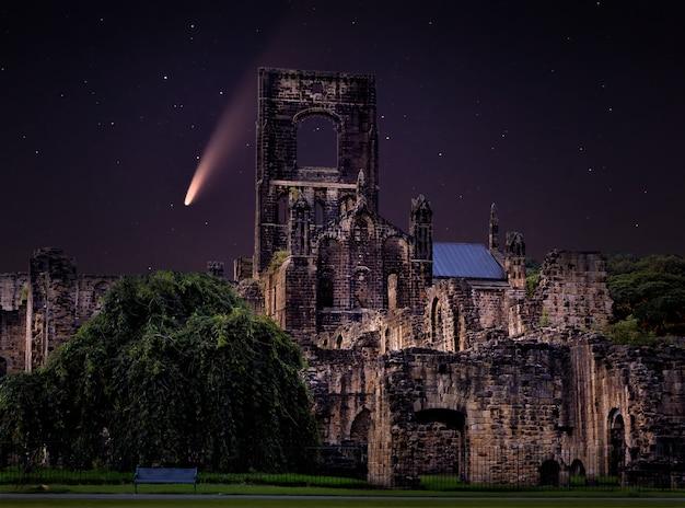 Nocne niebo i kometa nad zrujnowanym opactwem kirkstall w anglii. uk