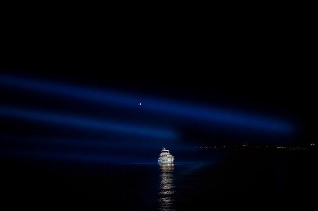 Nocne niebo nad białym jacht w morzu
