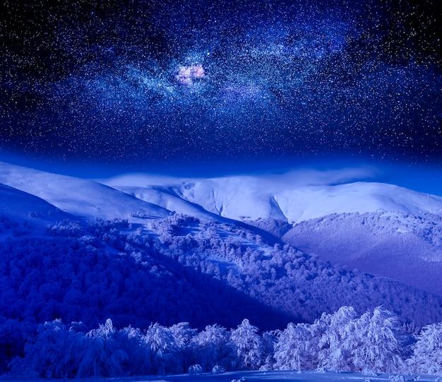 Nocne niebo nad ośnieżoną górą.