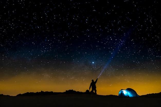 Nocne niebo z gwiazdami i sylwetką stojącego szczęśliwego człowieka z niebieskim światłem. kosmiczne tło - koncepcja podróży ludzi - bezpłatny kemping i przygoda na świeżym powietrzu - odkryj światowy styl życia