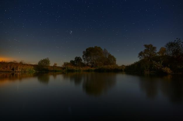 Nocne niebo z gwiazdami nad drzewami nad rzeką. krajobraz został sfotografowany na długiej ekspozycji.