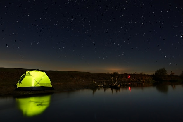 Nocne niebo z gwiazdami nad namiotem turystycznym nad rzeką