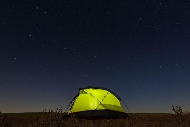 Nocne niebo z gwiazdami nad namiotem turystycznym