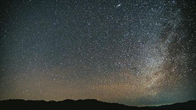 Nocne niebo z jasnymi gwiazdami i tło drogi mlecznej