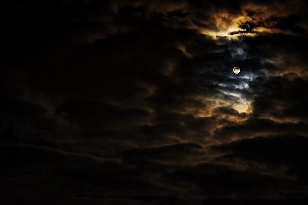 Nocne niebo z pełni księżyca i pięknymi chmurami.