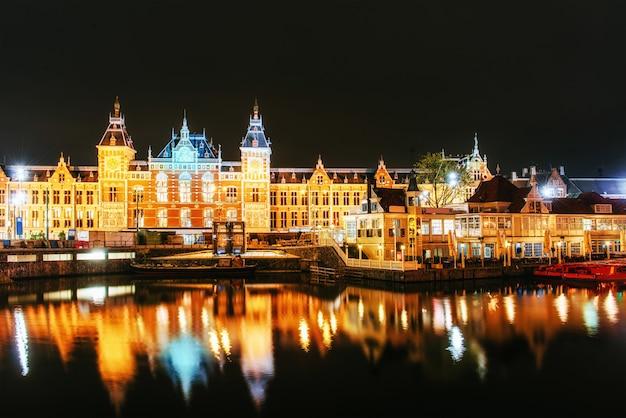 Nocne oświetlenie budynków i łodzi w pobliżu wody w kanale.
