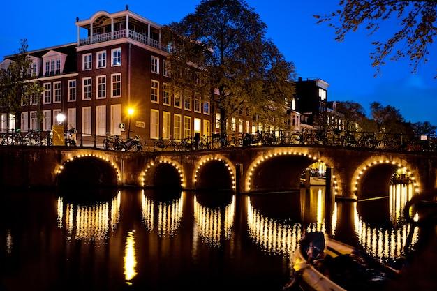 Nocne ujęcie miasta, wiele rowerów na moście nad kanałem w amsterdamie, holandia