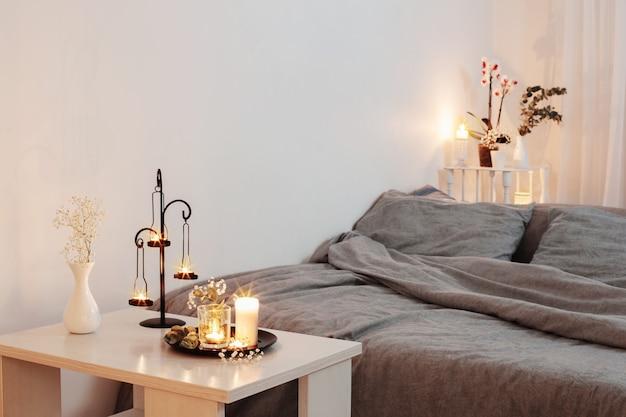 Nocne wnętrze sypialni z kwiatami i płonącymi świecami
