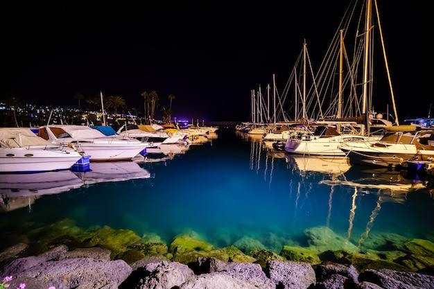 Nocne zdjęcie mariny z zacumowanymi łodziami i przezroczystą niebieską wodą, która odsłania skaliste dno. europa,