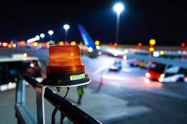 Nocne zdjęcie, zbliżenie, żółte światło ostrzegawcze, aby zwrócić uwagę na duży sprzęt lotniskowy. niewyraźne parkowanie samolotu