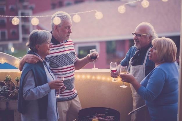 Nocni przyjaciele świętują razem z czerwonym i białym winem, bawiąc się razem z widokiem na miasto