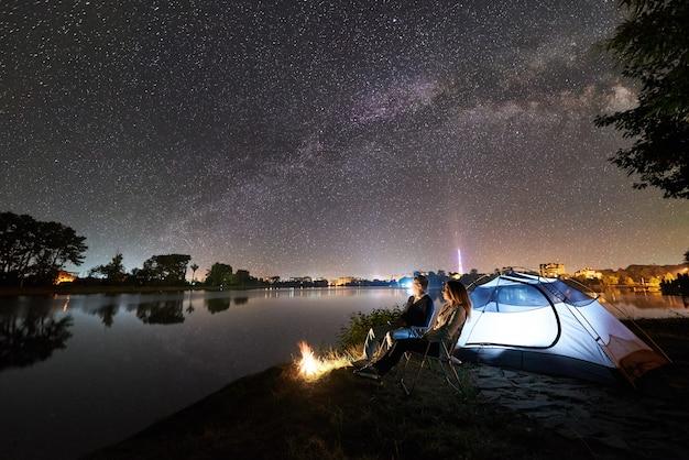 Nocny biwak na brzegu jeziora. mężczyzna i kobieta siedzą na krzesłach w pobliżu ogniska i świecącego namiotu, ciesząc się widokiem wieczornego nieba pełnego gwiazd i drogi mlecznej, spokojnej powierzchni wody, świetlistego miasta