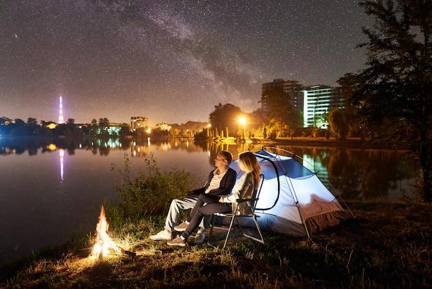 Nocny biwak na brzegu jeziora. mężczyzna i kobieta siedzą na krzesłach w pobliżu ogniska namiotowego, ciesząc się pięknym widokiem nocnego nieba pełnego gwiazd i drogi mlecznej