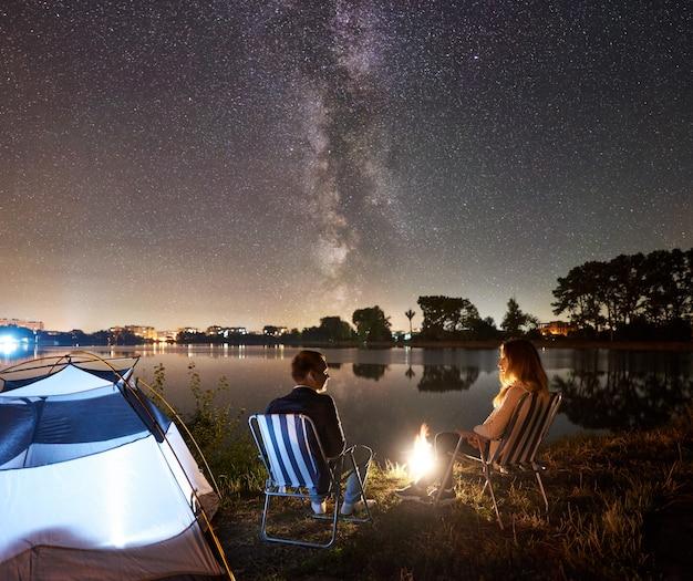 Nocny biwak na brzegu jeziora. mężczyzna i kobieta turystów siedzi na krzesłach w pobliżu ogniska, namiot. para turystów korzystających z nocnego nieba pełnego gwiazd i drogi mlecznej, spokojna powierzchnia wody, światła miasta