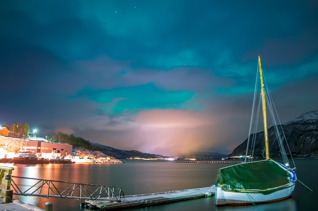 Nocny fiord w zimie norwegia. łódź jest przy molo. światła wioski na horyzoncie, otoczonej ośnieżonymi górami. mała zorza polarna na niebie