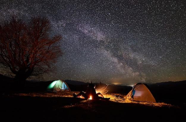 Nocny kemping. piesi odpoczywający przy ognisku pod rozgwieżdżonym niebem
