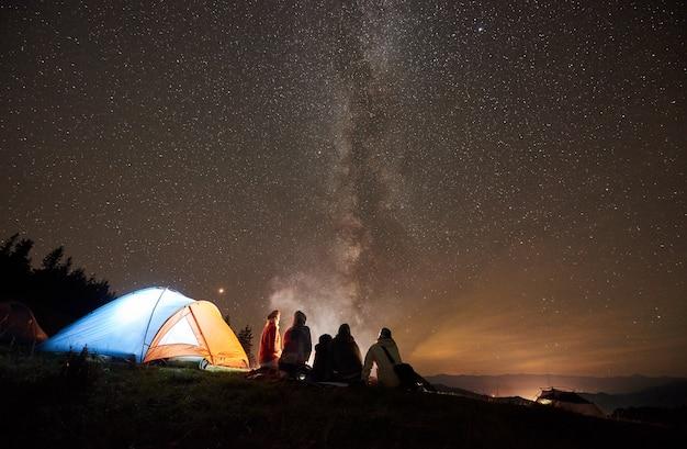 Nocny kemping z ludźmi przy ognisku pod rozgwieżdżonym niebem
