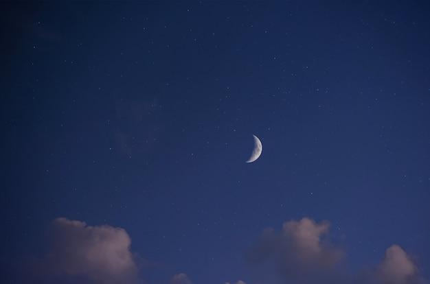 Nocny krajobraz, ciemnoniebieskie gwiaździste niebo, widok na jasny księżyc